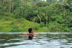 在无限水池的年轻亚洲女孩游泳有美丽的景色 她被拍从后面的照片 免版税图库摄影
