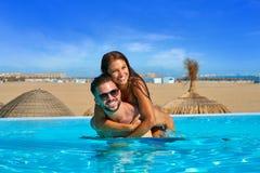 在无限水池的旅游夫妇肩扛 库存图片