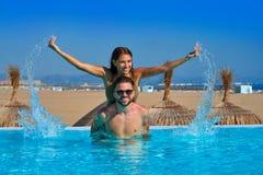 在无限水池的旅游夫妇肩扛 图库摄影