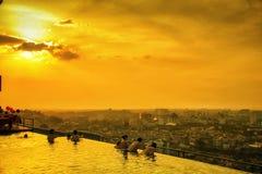 在无限水池的日落游泳 库存图片