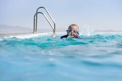 在无限池的男孩游泳 免版税库存图片