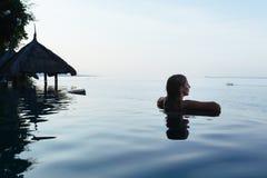 在无限游泳池的妇女黑剪影 免版税库存照片