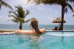 在无限水池的妇女游泳在海洋旁边 免版税库存图片