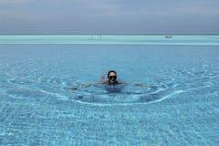 在无限水池的妇女游泳在马尔代夫 免版税库存照片