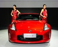 在日产370Z交谊厅汽车的时装模特儿 免版税库存图片