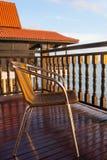 在日出光的邀请的椅子在海的Baclony 库存照片