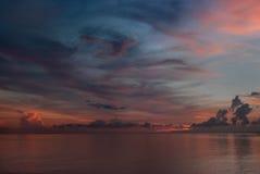 在日出前的清早在海洋:蓝色云彩在天空,太阳的油漆扭转并且创造一个巨大的漩涡的图片 库存照片