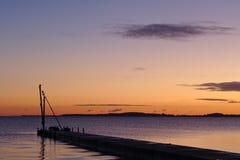 在日出前的码头与鸟坐一台小起重机现出轮廓反对早晨天空 免版税库存照片