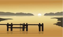 在日出在有码头剪影的海 免版税图库摄影