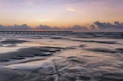 在日出或日落的海洋码头 免版税库存图片