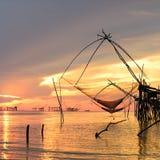 在日出期间的方形的抄网抓住鱼 免版税库存图片
