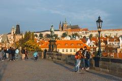 在日出期间的游人参观查理大桥,布拉格 免版税库存照片