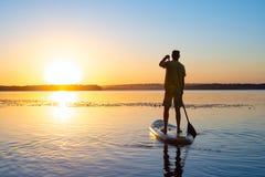 在日出期间,供以人员在一口板的风帆在一条大河 免版税图库摄影