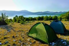 在日出期间的两个帐篷在岩石地面上 库存图片