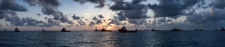 在日出期间的近海船定住 库存图片