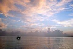 在日出期间的更加可疑的小船在海 在颜色下的相当海洋 库存照片