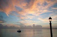 在日出期间的更加可疑的小船在海 在颜色下的相当海洋 图库摄影