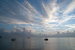 在日出期间的更加可疑的小船在海 在颜色下的相当海洋 免版税库存图片