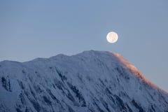 在日出期间的满月在背景积雪覆盖在喜马拉雅山山在尼泊尔 库存图片