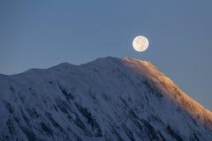 在日出期间的满月在背景积雪覆盖在喜马拉雅山山在尼泊尔 免版税库存照片