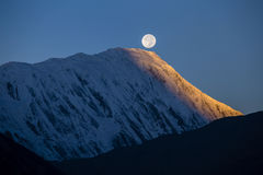 在日出期间的满月在背景积雪覆盖在喜马拉雅山山在尼泊尔 免版税图库摄影