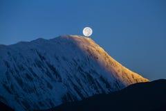 在日出期间的满月在背景积雪覆盖在喜马拉雅山山在尼泊尔 图库摄影