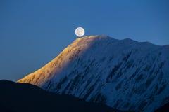 在日出期间的满月在背景积雪覆盖在喜马拉雅山山在尼泊尔 免版税库存图片