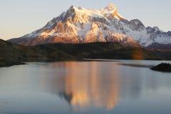 在日出期间的Majestic Cuernos del潘恩反射在湖Pehoe在托里斯del潘恩国家公园, Patagon 免版税库存照片