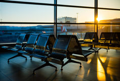 在日出期间,在机场大厅里换下场 图库摄影