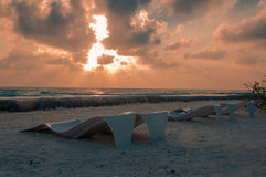 在日出期间,太阳通过云彩发出光线显示 免版税库存图片