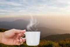 在日出期间,递拿着在山背景被弄脏的层数的热的咖啡杯  免版税图库摄影