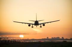 在日出期间,飞机登陆 免版税图库摄影