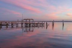 在日出桃红色天空的一个老码头  免版税库存图片