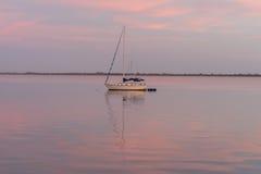 在日出桃红色天空的一条风船  库存图片