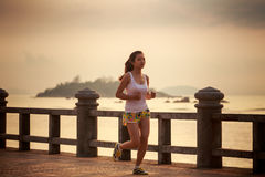 在日出的亚洲女孩奔跑 免版税库存照片