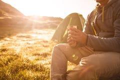 年轻在日出的人饮用的茶在山 免版税库存图片