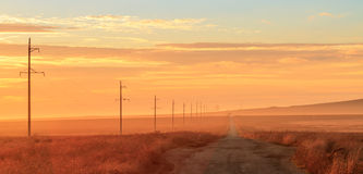 在日出的农村路 库存照片