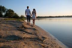 在日出的夫妇在海滩 库存图片