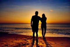 在日出的夫妇在海滩 免版税库存图片