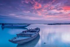 在日出的小船在湖 免版税库存图片