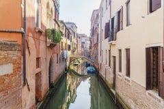 在日出的早晨威尼斯点燃与小船和明亮的大厦 免版税库存图片