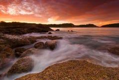 在日出的普吉岛海滩与在前景的有趣的岩石 图库摄影
