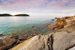 在日出的普吉岛海滩与在前景的有趣的岩石 免版税图库摄影