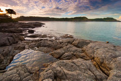 在日出的普吉岛海滩与在前景的有趣的岩石 库存图片