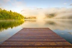 在日出的木着陆跳船 在湖Bohinjsko的有雾的早晨,斯洛文尼亚 免版税库存照片