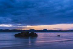 在日出的海洋岩石在海滩 库存图片