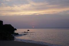 在日出的海洋 atlantes 沙滩和早晨天空的颜色 库存照片