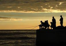 在日出的渔夫剪影在船坞 免版税库存图片