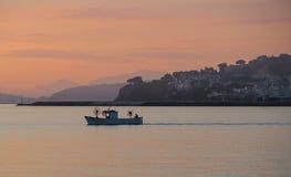 在日出的渔船在海 免版税库存图片