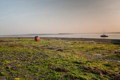 在日出的渔船处于低潮中在出海口 库存图片